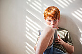 Boy with red hair sitting on floor in sunny room, holding digital tablet.