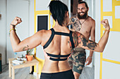 Bearded tattooed man with long brunette hair and woman with long brown hair showing her muscles standing indoors.