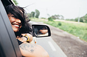 Smiling woman with long brown hair and tattoos looking out of car window.