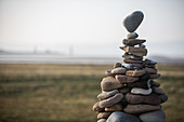 A tower of stones of various sizes stacked in a cairn, the top stone balancing on a point.