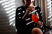 Cropped shot of happy young woman drinking spritz cocktail in boutique hotel restaurant, Italy