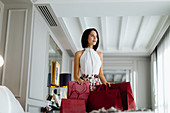 Fashionable woman with shopping bags in suite