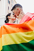 Portrait of young lesbian couple standing on a street, wrapped in rainbow flag, kissing.