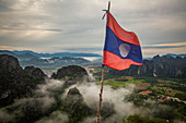 Laos flag with a view of karst landscape from Vang Vieng, Laos, Asia