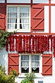 France, Pyrenees Atlantiques, Pays Basque, Espelette, pepper drying on the facade of a traditional house