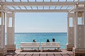 France, Alpes Maritimes, Nice, the Baie des Anges, womans sitting on a bench of the Promenade des Anglais