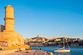 France, Bouches du Rhone, Marseille, the entrance to the Vieux Port and the Fanal Tower of Fort Saint Jean at sunset