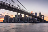 View of Brooklyn Bridge to New York City,Manhattan island,at dawn,flat calm water.