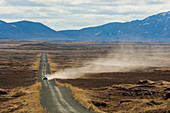 Vehicle leaving trail of dust on gravel road,Dettifoss,Iceland