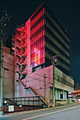 Red light reflected on facade of office building at night,view from the street,Osaka,Japan
