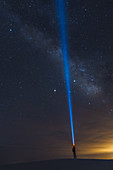 Man shining torch into sky,White Sands National Monument,New Mexico,US
