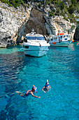 Tourists snorkelling at the Blue Caves, Paxos, Ionian Islands, Greek Islands, Greece, Europe