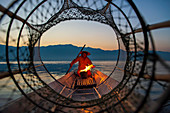 Intha leg rowing fisherman viewed through net on Inle Lake, Shan State, Myanmar (Burma), Asia