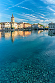 Clock tower of St. Peter church mirrored in the turquoise water of Limmat River, Lindenhof, Zurich, Switzerland, Europe