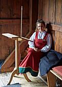 Young woman in traditional costume in the Ringebu Stave Church, Stavkyrkje Ringebu, Ringebu, Gudbrandsdalen, Rondanevegen, Oppland, Norway, Europe