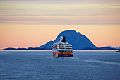 Encounter with the Hurtigruten ship Nordnorge at dawn, Rödöyfjord, Helgeland coasts, Nordland, Norway, Europe