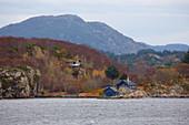 Landscape with a blue house in the Hjeltefjorden north of Bergen, Hordaland Province, Vestlandet, Norway, Europe