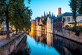 A tranquil canal scene in Bruges, with the spires of the Stadhuis (Town Hall) in the distance, Bruges, Belgium, Europe
