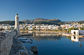 View along sea wall of the Venetian Harbour, 16th century lighthouse prominent, Rethymno (Rethymnon), Crete, Greek Islands, Greece, Europe