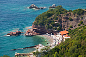 View from clifftop over sheltered cove of clear turquoise water, Sveti Stefan, Budva, Montenegro, Europe