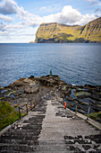 View down the stairs to the bronze statue of the seal woman, created after the folk tale in which the village of Mikladalur was cursed, Mikladalur, Kalsoy, Faroe Islands, Denmark.