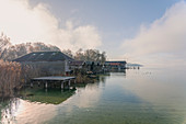 View from the jetty in Percha to boathouses on Lake Starnberg to the south towards the mountain, Starnberg, Bavaria, Germany.