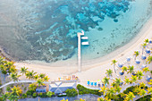 Jetty and sunbeds on palm-fringed beach washed by Caribbean Sea from above by drone, Morris Bay, Old Road, Antigua, Leeward Islands, West Indies, Caribbean, Central America