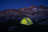 Tent lit by a headlamp with the Bagüeñola or Eriste peaks in the background. Posets-Maladeta Natural Park. Aragon. Spain.