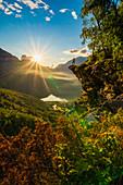 Rear view of man on top of rocks admiring Geiranger at sunset, Stranda municipality, Sunnmore, More og Romsdal county, Norway, Scandinavia, Europe