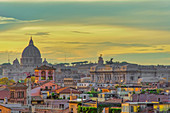 Rooftops landscape panorama with traditional low-rise buildings and St. Peters Basilica dome, golden hour elevated view, Rome, Lazio, Italy, Europe