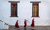 Three Buddhist monks carrying food bowls, Kyichu Temple, Bhutan, Asia