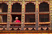 Portrait, mature Buddhist monk looking out of window, Punakha Dzong, Bhutan, Asia