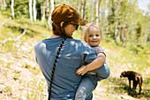 Frau hält kleine Tochter auf dem Arm in der Natur