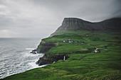 Denmark, Faroe Islands, Gasadalur village, Mulafossur Waterfall, Cliffed coast and ocean