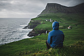 Denmark, Faroe Islands, Gasadalur village, Man sitting and looking at cliffed coast and ocean