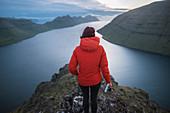 Denmark, Faroe Islands, Gjgv, Woman standing on Klakkur mountain and looking at fjord