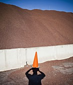 Heap of sand or gravel and shadow of a person