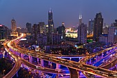 Elevated road junction and skyline of Shanghai, China at dusk.