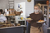 Blond waitress wearing face mask working in a cafe, carrying plates of food.