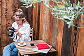 Young blond woman alone at an outdoor table, looking at digital camera display.