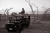 Woman standing on top of 4x4 parked in the Moremi Reserve, Botswana.