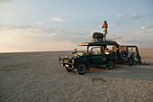 Man standing on top of 4x4 parked on the Makadikadi Salt Pans in Botswana.