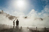 Two people in rising mist at a thermal pool site