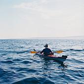Man sea kayaking in Puget Sound at dusk
