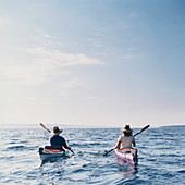 Middle aged man and woman sea kayaking on calm waters