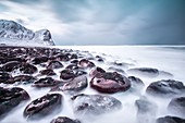 Rocks on the beach modeled by the wind surround the icy sea Unstad Lofoten Islands Norway Europe