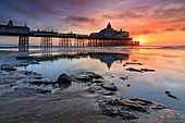 Sunrise and Eastbourne Pier reflected in a  large pool of water on the adjacent beach.  The image was captured from a low vantage point on a wind free morning in early March.