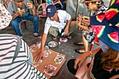 Street gambling den playing dice based betting and a homemade board, back streets, Old quarter, Hoi An, Quang NAm Provence, Vietnam, Asia