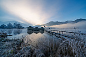 Three fishing huts on the Kochelsee in the morning light near Schlehdorf, Bavaria, Germany.