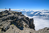Two people stand on the summit of Grande Dent de Morcles with summit cross, Mont Blanc in the background, Dent de Morcles, Bernese Alps, Vaud, Vaud, Switzerland